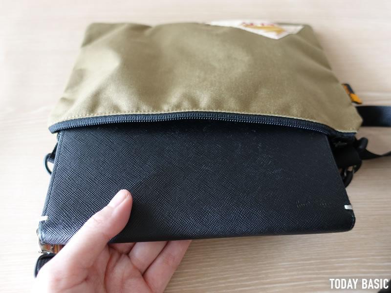 ケルティのサコッシュ・ヴィンテージ フラットポーチSに長財布を収納しようとしている画像