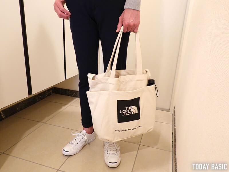 ノースフェイスのユーティリティートートバッグを手持ちしている画像